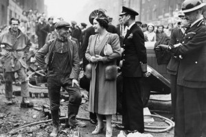 King George VI and Queen Elizabeth visit Londoners after aircraft bombings of the city.